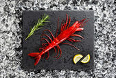 Fresh big red shrimp on ice on a black stone table top view — Stock Photo