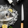 Fresh dorado fish on ice on a black stone table top view — Stock Photo #63433013