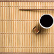 Chopsticks and bowl with soy sauce on bamboo mat — Stock Photo #65119329