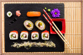 Sushi on black stone plate on a bamboo mat top view — Stock Photo