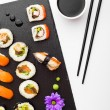 Sushi, chopsticks and soy sauce on black stone plate top view — Stock Photo #68416533