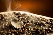 Roasting coffee beans with smoke on dark background — Stock Photo
