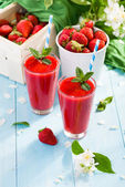 Strawberry smoothie and flower petals on blue background — Stock Photo