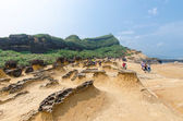 Honeycomb weathering and mushroom rocks in Yehliu Geopark, Taiwan.People can seen exploring around it. — Stock Photo