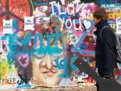 A man with a guitar is looking for new paintings Lennon Wall in Prague on Kampa — Stock Photo