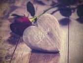 Vintage foto van hart op een houten achtergrond met rode roos. — Stockfoto