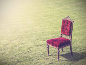 Vintage antique old red chair on green grass, abstract backgroun — Stockfoto