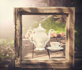 Vintage picture of tea set in garden in wooden frame. — Stockfoto