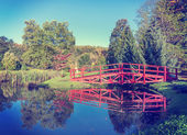Vintage retro filtered picture of red bridge in garden. — Stock Photo
