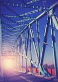 Vintage stylized photo of a steel bridge with sun light.  — Stock fotografie