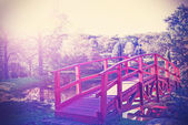 Vintage filtered picture of red bridge in garden.  — Stock Photo