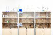 Different laboratory glassware and equipment on shelves. — Stock Photo