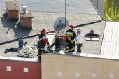 Firemen checking chimney of a heating system on the roof. — Stock Photo