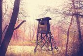 Vintage filtered photo of hunting pulpit in forest. — Stock Photo