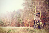 Retro filtered photo of a hunting pulpit in forest. — Stock Photo