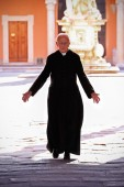 Priest walking on the churchyard in the old town of Pisa. — Stock Photo