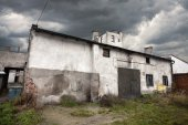 Sullen abandoned warehouse with stormy sky. — Stock Photo