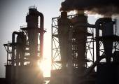 Smoky chimneys silhouettes against sun. Air pollution concept. — Stock Photo
