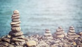 Vintage retro hipster style image of stones on beach. — Stockfoto