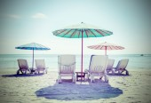 Retro filtered picture of beach chairs and umbrellas. — Stock Photo