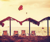 Vintage filtered picture of beach and paragliders at sunset. — Stock Photo