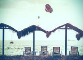 Retro vintage filtered picture of beach and paragliders at sunse — Stock Photo