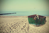 Retro filtered picture of an old rusty steel boat on the beach. — Stock fotografie
