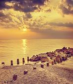 Retro getönten dramatischen Sonnenuntergang über Meer und felsigen pier. — Stockfoto