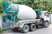 Concrete mixer truck with green cab over trees — Stock Photo