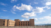 Soft white clouds against blue sky and brick building — 图库照片