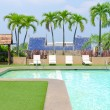 Swimming pool with green grass and palm at hotel close up — Stock Photo #55484815