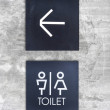 Unisex restroom or Toilet and arrow sign on  concrete wall style — Stock Photo #78413654