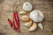 Dried red chili pepper and fresh garlic on wooden background — Stock Photo
