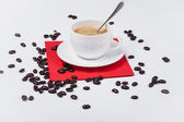 Cup of coffee on fabric with coffee-beans — Stock Photo