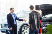 Car salesman giving key of  new car to  young  owners — Stock Photo
