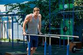 Workout, sportsman pull ups on the horizontal bar — Stock Photo