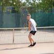 Young man play tennis outdoor on orange  court — Stock Photo #79261098