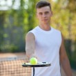 Young man play tennis outdoor on orange  court — Stock Photo #79261140