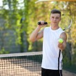 Young man play tennis outdoor on orange  court — Stock Photo #79261156
