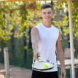 Young man play tennis outdoor on orange  court — Stock Photo #79261164