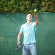 Young man play tennis outdoor on orange  court — Stock Photo #79261824