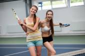Young women playing doubles  tennis at the court — Stock Photo
