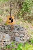 Guitarra acústica en una roca — Foto de Stock