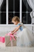 Little girl in a beautiful dress unpacks Christmas gift — Stock Photo