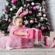 Little girl in a beautiful dress is holding a Christmas gift — Stock Photo #60429481