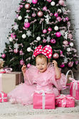Little girl rejoices gifts near a Christmas tree — Stock Photo
