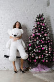 Beautiful girl with a soft toy near a Christmas tree — Stock Photo