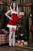Beautiful woman in Santa Claus clothes near a Christmas tree wit — Stock Photo