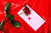 Red rose on satin cloth, an envelope with a wish — Stockfoto