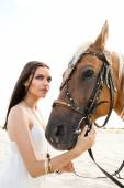 Beautiful woman in white dress posing with horse against desert — Stock Photo